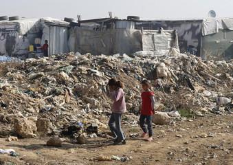 Girls walk near garbage inside Fayda Syrian informal refugee camp in Zahle, Lebanon
