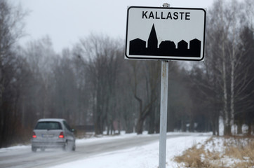 A car drives past a town sign next to the Estonian-Russian border near Kallaste
