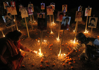 People light candles under the portraits of the Godhra riots victims during a candlelight prayer ceremony in Ahmedabad