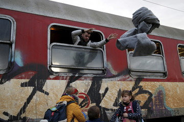 A migrant throws blankets from a train window as migrants are returned to a camp near the Macedonian-Greek border in Gevgelija, Macedonia