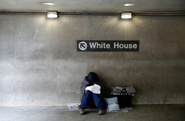 A homeless person sits in a subway station near the White House in Washington