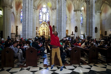 Boy plays with a balloon as he waits for the start of a distribution of free toys for low-income families and a picture on the lap of one of the Three Wise Men at Almudena Cathedral in Madrid
