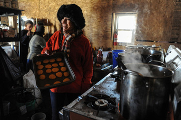 CJ Brafford, Oglala Sioux from the Pine Ridge Reservation, pulls a sheet of cookie out of the oven in the Oglala Sioux kitchen in an encampment during a protest against plans to pass the Dakota Access pipeline near the Standing Rock Indian Reservation