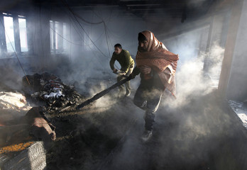 A civilian and a firefighter try to salvage useful materials after a fire in Srinagar