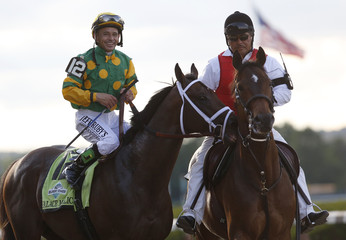 Palace Malice, with jockey Mike Smith in the irons, nudges another horse as they are escorted after winning the 145th running of the Belmont Stakes, the final leg of horse racing's triple crown, at Belmont Park in Elmont