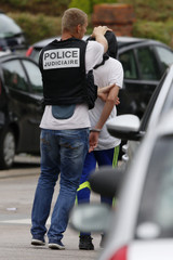 French judicial investigating police apprehends a man during a raid after a hostage-taking in the church in Saint-Etienne-du-Rouvray near Rouen in Normandy