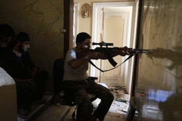 A Free Syrian Army sniper takes his position at the Seif El Dawla neighborhood in Aleppo
