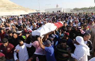 Ministry of Interior officials, family members and well-wishers carry the body of Abdullwahid Sayed Mohammed al-Baloushi during his funeral procession in Hananiya cemetery in Riffa