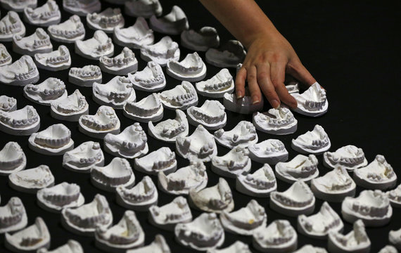 A gallery assistant lays out dental casts from artist Gina Czarnecki's The Wasted Works exhibition at the Science and Industry Museum in Manchester,