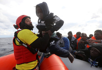 A lifeguard pulls a migrant child to a rescue boat from an overcrowded raft, as lifeguards from the Spanish NGO Proactiva Open Arms rescue all 112 on aboard, some 36 nautical miles off the Libyan coast