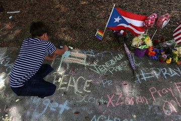 A child draws a U.S. flag on the sidewalk in chalk by a Puerto Rico flag at a makeshift memorial that is across the street from Pulse night club following last week's shooting in Orlando