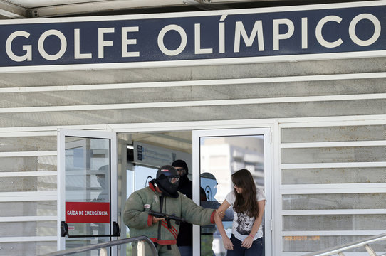 A man role-playing as a kidnapper holds onto a woman role-playing as a kidnap victim during a crisis simulation exercise conducted by Brazil's BOPE at the Golf Olympic bus station in Rio de Janeiro