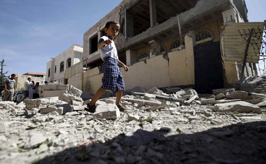 Boy walks past a house damaged by a Saudi-led air strike in Yemen's capital Sanaa