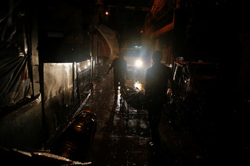Heavy rain pours as funeral workers take away the body of a man killed by unidentified gunmen riding motorcycles in Manila