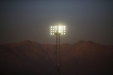 The lights of Estadio Monumental are pictured with the Los Andes Mountain in the background in Santiago