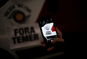 "Demonstrator takes a picture of a sign reading ""Out Temer"" on a military police car during a protest against Brazil's President Michel Temer in Sao Paulo"