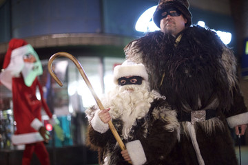 Father and son are pictured dressed as Belsnickle while a giant Santa strolls in the background during a ceremony to decorate a scraggly Christmas tree in Reading