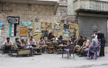 """Members of the """"Liwaa al-Sultan Mrad"""" brigade, operating under the Free Syrian Army, sit together as they rest in Aleppo's Bustan al-Basha district"""