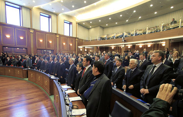 Members of parliament take the oath during its first session in Pristina