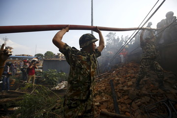 Members of the Nepalese Army lift a water pipe over their heads as part of an effort to put out a fire which broke out at the Nepal Electricity Authority (NEA) distribution center at Ratnapark in Kathmandu