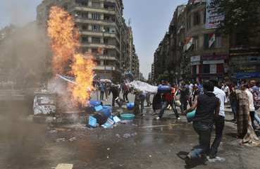 Protesters try to douse a fire  after a cooking gas canister exploded in an accident at Tahrir square in Cairo
