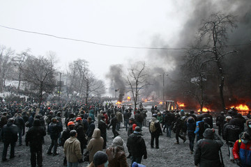 Pro-European protesters are pictured as black smoke from burning tyres rises in the background during clashes with riot police in Kiev