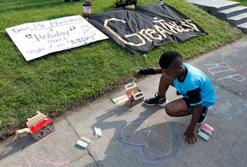 Ferlandas Wright draws with chalk on the sidewalk before a neighborhood celebration to celebrate the life of the late Muhammad Ali, former world heavyweight boxing champion at Ali's childhood home in Louisville