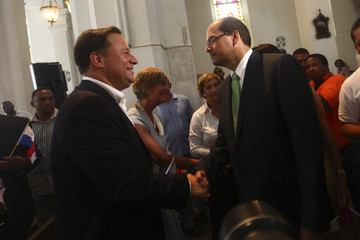 Carlos Varela, presidential candidate for the Panamenista Party, shakes hands with Domingo Arias, presidential candidate of the ruling Democratic Change  party, during a mass inside Metropolitan Cathedral in Panama City