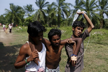 Rohingya migrants, who recently arrived in Indonesia by boat, carry an IV drip as they help a fellow migrant to walk inside a temporary compound for refugees in Aceh Timur regency