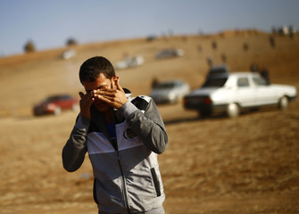 A man wipes his eyes after Turkish military fired tear gas in an attempt to clear a hill of observers near Mursitpinar crossing on Turkish-Syrian border