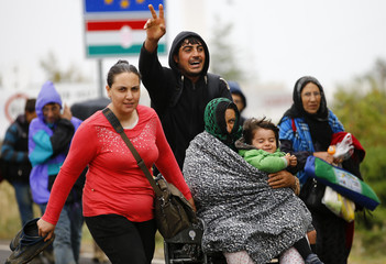 A migrant flashes victory sign as he pushes an injured woman and a child in a wheelchair as they cross the border from Hungary in Nickelsdorf