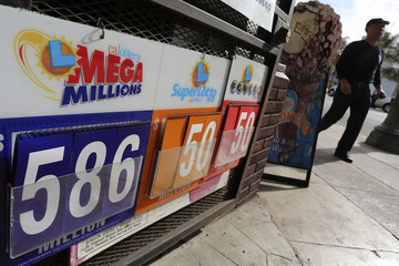 A man walks past a Mega Millions lottery sign in Los Angeles