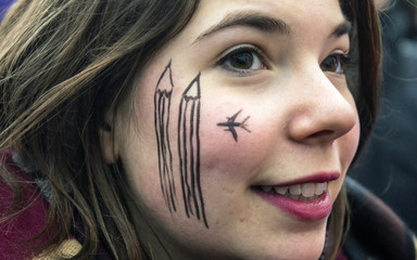 A woman wears a cartoon painting on the face during a silent protest for the victims of the shooting at the Paris offices of weekly newspaper Charlie Hebdo, at the Pariser Platz square in Berlin