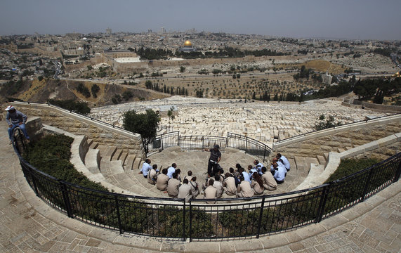Israeli soldiers listen to a guide on the Mount of Olives as the Dome of the Rock and Al-Aqsa mosque are seen in the background in Jerusalem's Old City