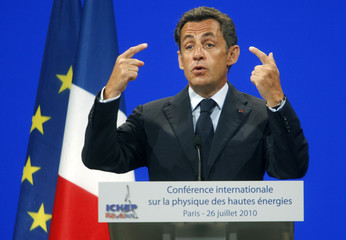 France's President Nicolas Sarkozy gestures as he speaks to scientists during the 35th International Conference on High Energy Physics in Paris