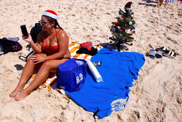 Irish backpacker Genna Woods talks to relatives on her phone as she sits next to her small Christmas tree she planted in the sand as she celebrates Christmas Day at Sydney's Bondi Beach in Australia