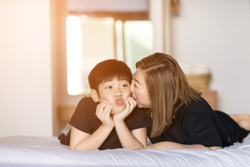 Mother kiss her son in bedroom