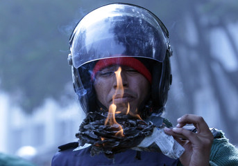 A member of police inhales smoke from papers set on fire during a clash with teachers in front of press club in Dhaka.