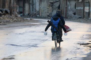 A rebel fighter carries food while riding a bicycle and carrying his weapon on his back in rebel-held besieged old Aleppo