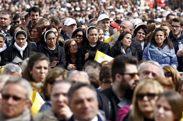 Faithful attend a mass celebrated by Pope Francis in Plebiscito square during his pastoral visit in Naples