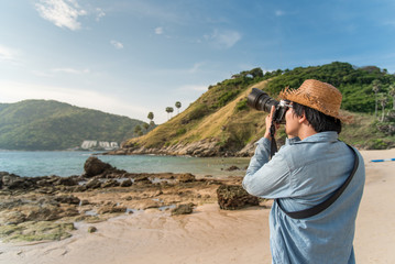 young Asian man photographer with jean shirt and straw hat take photo of tropical island beach and turquoise sea, seascape background for summer holiday and vacation travel concepts