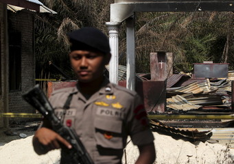 A policeman holds a rifle as he stands guard in front of a burned church at Suka Makmur Village in Aceh Singkil