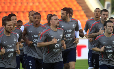 France's national soccer team warms up during a training session in Minsk