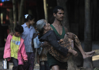 Myanmar refugee, who crossed over from Myanmar to Thailand when a battle erupted between Myanmar's soldiers and rebels, carries his relative at the Thai border town of Mae Sot