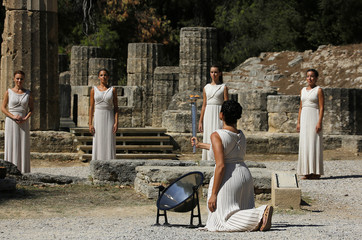 Greek actress Menegaki lights a torch during a dress rehearsal for the torch lighting ceremony of the Sochi 2014 Winter Olympic Games at the site of ancient Olympia in Greece