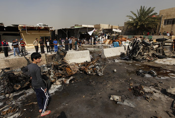 Residents gather at the site of a car bomb attack in the Ameen district in Baghdad February
