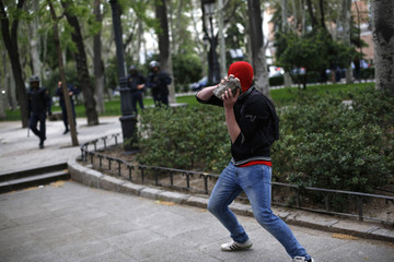 A protester throws a stone at riot police during a planned demonstration against the government in Madrid