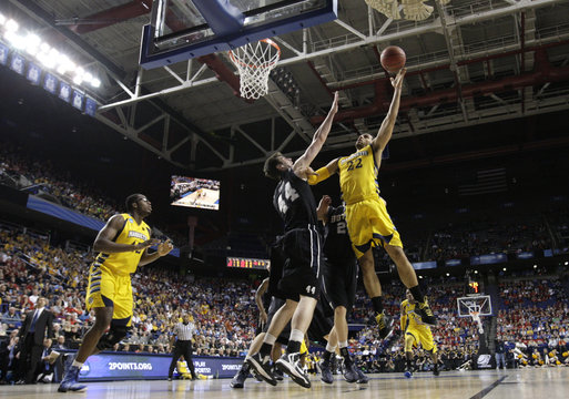 Marquette University's Lockett fights to get shot off under pressure from Butler University's Smith during third round NCAA basketball game in Lexington
