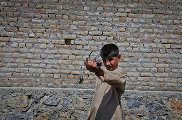 A boy displays debris, the remains of a firefight, nearby the compound where al Qaeda leader Osama bin Laden was killed in Abbottabad