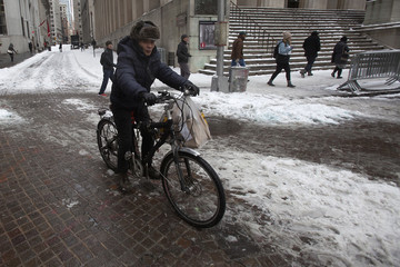 A delivery person on a bicycle rides in front of the New York Stock Exchange, open during Winter Storm Juno, in the Manhattan borough of New York
